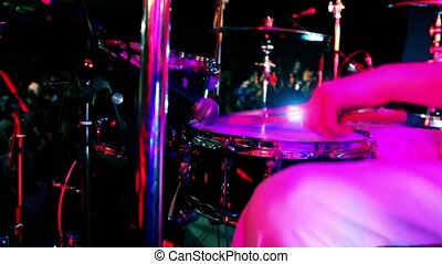 Drummer in white costume holds drumsticks and play, closeup...