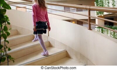 Little girl walks upstairs by circular staircase in multiple...