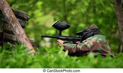 Boy paintball player sits in ambush with gun at background...
