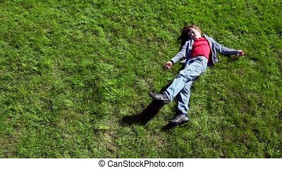 Little boy lay on grass plot and then rolls away, view from...