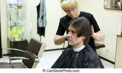 Hairdresser cuts hair to man with long hair by clipper -...