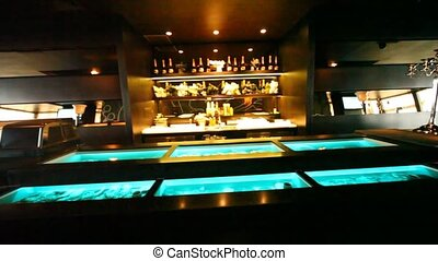 Aquariums with oysters are built in bar counter and on showcase there is champagne in oyster bar