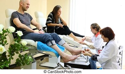 Cosmeticians do hardware pedicure to man and  woman