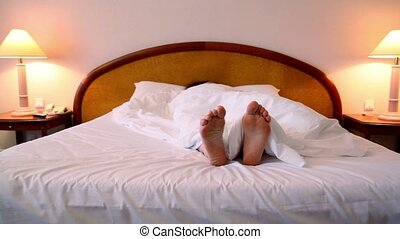 Woman lay in bed under blanket and moves bootless feet -...