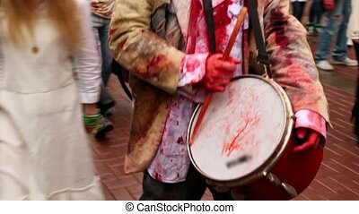 Drummer walk among people in bloody torn clothes and plays