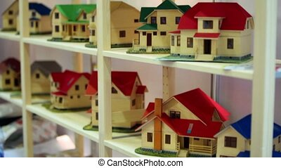 Lot of models of houses on wooden shelves, upward motion