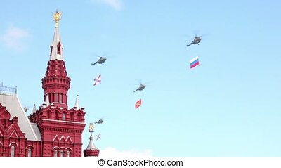 Five helicopters with flags fly over spire of State...