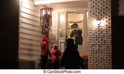 Trick or treating in Halloween nigh - Three children with...