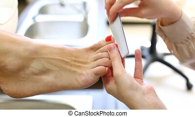 Beautician adjusts form of fingernails of woman by means of file for nails