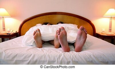 Couple lays in bed under blanket - Couple lays in bed under...