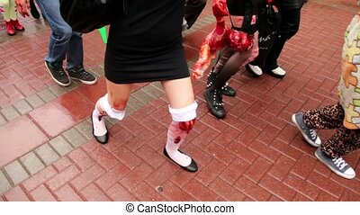 Girls zombies walk by pavement with bandage on legs and...