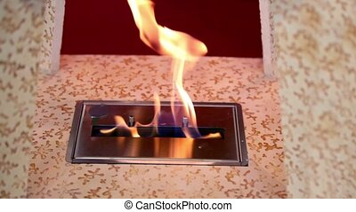 Tongues of flame from slot in plate inside wooden frame