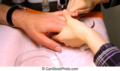 In course of manicure cosmetician rubs butter for nails in...