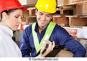 Supervisor Showing Clipboard To Foreman - Female supervisor...