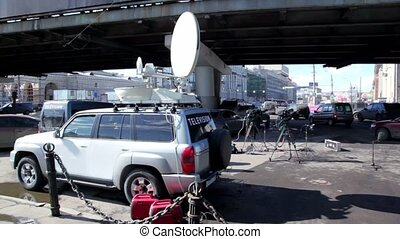 Car with satellite dish on roof and other tv equipment near at background of city traffic