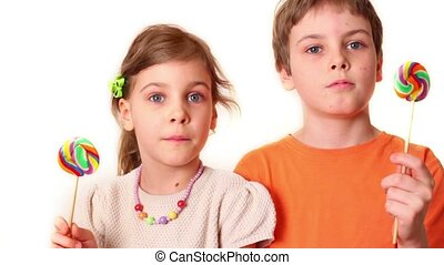 Two kids boy and girl hold lollipops and then look on each other isolated on white background