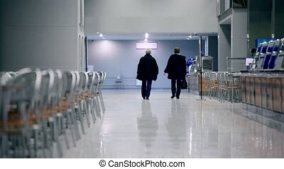 Elderly couple walk away in cafe, empty chairs stand on both...