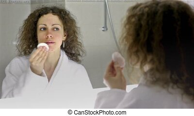 Woman wearing white bathrobe cleans face in front of mirror...