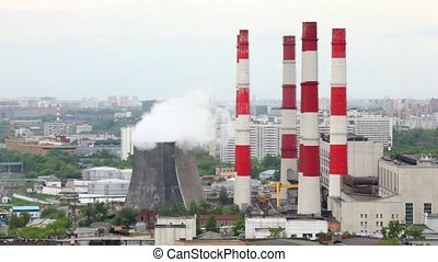 Pipes of thermal power station stand against city landscape