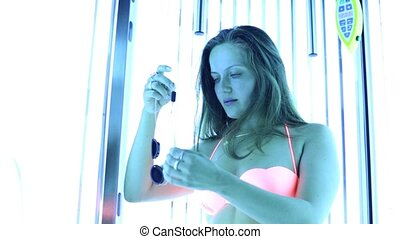Young woman stand in solarium and sunbathes in salon