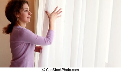 Young woman draws curtains and opens window, closeup view