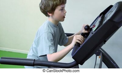 Little boy walks on treadmill and looks to panel with hands...