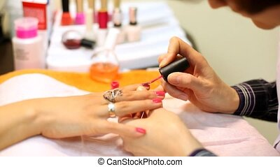 Cosmetician accurately covers nails of client with pink nail...
