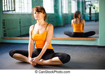 Mature woman exercising yoga in a gym