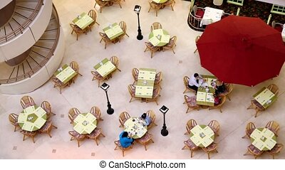 Several people sit at tables on cafe, view from above