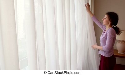Young woman draws curtains and opens window with city street...