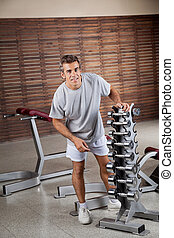 Man Standing By Dumbbells In Rack