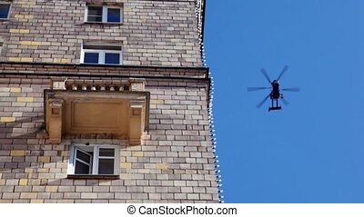 helicopter fly at blue sky, house wall with windows and...