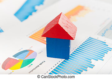 Real estate market concept with graphs and house from toy...