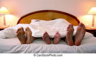 Family lay in bed under blanket and move bootless feet,...
