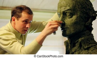 Sculptor Denis Petrov puts pieces of clay on nose of...