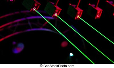 Several lasers hang under ceiling and emit green rays