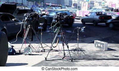 Television equipment stand near road with city traffic