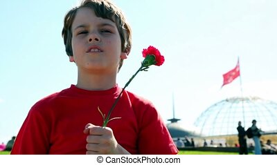 Little boy with red flower stand at background of red flag...