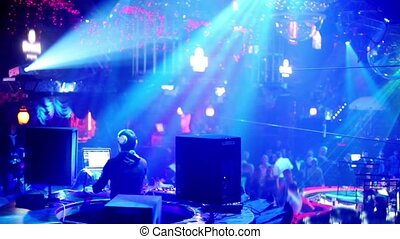 People in night club with illumination, dj on workplace
