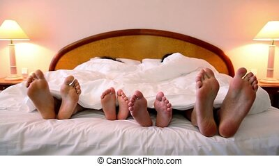 Father and mother with their kids lay in bed under blanket and move bootless feet