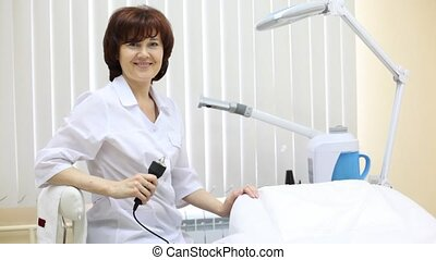Woman-cosmetician sits on workplace also invites to...