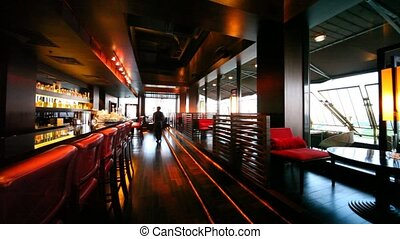 Restaurant lounge is decorated in red-brown tones and lamps...