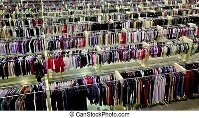 One woman watch goods among lot of clothes in shop - One...