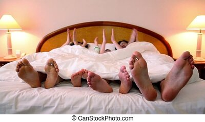 Family makes various gestures by hands  in bed under white blanket and then moves barefoot feet