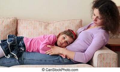 Little girl lies on her mother legs at sofa, closeup view