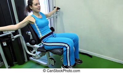Young woman sits and exercises on training equipment