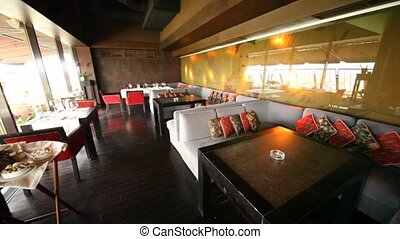 Restaurant lounge is filled by table of black color and by sofas with color throw pillows