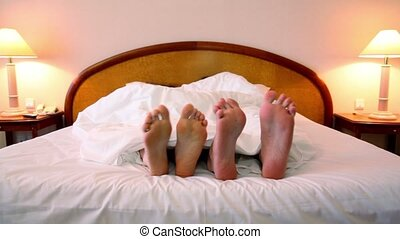 Man with woman lay in bed under blanket and moves shoeless...