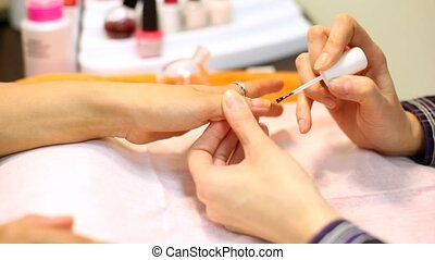 Cosmetician colors nails of woman its fingers are decorated...