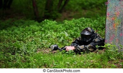 Boy paintball player lies with gun in ambush on grass near...